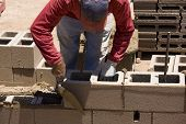 stock photo of cinder block  - Migrant worker building cinder block wall in desert setting - JPG