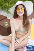 Beautiful Sexy Young Smiling Woman With Long Hair In A Bikini, Yellow Sunglasses And Big Hat Sitting poster