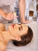 Ultrasound therapy for skin tightening in beauty spa salon. Beautician does procedure by electric de poster