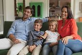 Front view of happy Caucasian family watching television in living room at home poster