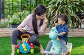 Asian Single Mom With Son Are Playing With Toy And Eating Together When Living In Front Lawn Of Mode poster