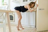 Hungry Woman Looking For Food In White Retro Refrigerator In Bright Apartments poster