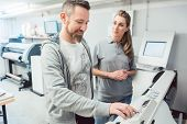 Two employees in advertising agency operating large format printer on touchscreen  poster