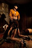 stock photo of flogging  - Strict cowboy with black Leather Flogging Whip in his hand clutching bondwoman between his legs - JPG