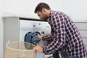 Side view of Caucasian man putting dirty clothes into the washing machine in a comfortable home poster