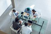 High angle view of diverse medical team discussing x-ray report over digital tablet at table in hosp poster