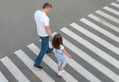 A Man And A Small Child On A Zebra Crossing Trespassing By Crossing The Street. In The Summer On The poster