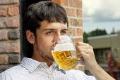 stock photo of bing  - Portrait of a sad young man drinking beer out of glass bok on pub