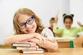 Cheerful Child Posing While Sitting At Desk And Lying On Books In Classroom. Happy Girl Wearing Glas poster