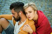 Enjoying Music. Feeling Free And Stylish. Man And Woman Modern Clothes For Youth Relaxing Outdoors.  poster