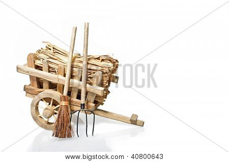 Old handcart with straw and tools