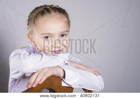 portrait of a schoolgirl on the chair in studio