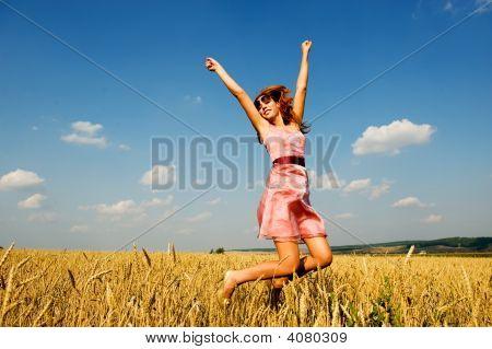 Happy Woman Jumping In Golden Field