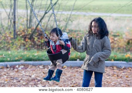 Girl Pushing Toddler On Swing In Autmn