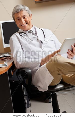 Portrait of happy mature male doctor holding digital tablet while sitting by desk at clinic