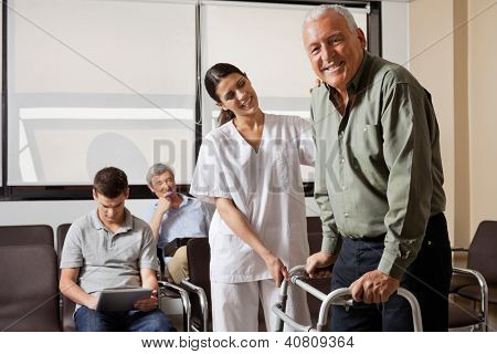 Portrait of senior man being assisted by female nurse to walk Zimmer frame with people sitting in background