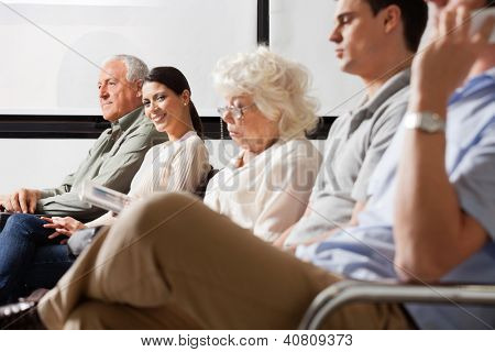 Portrait of mid adult female smiling while sitting amidst other people in hospital lobby