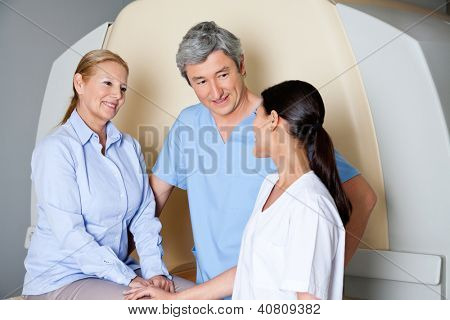 Multiethnic radiologic technicians with mature female patient smiling at them