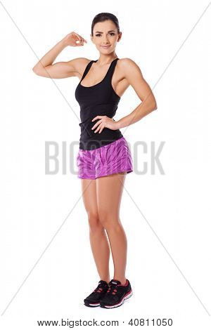 Attractive fit athletic young woman wearing shorts and a gym top flexing her arm and showing off her biceps