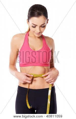 Young attractive slim female athlete measuring her waist with a tape meaure to check on her weightloss isolated on white