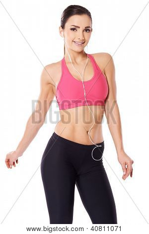 Beautiful shapely fit young woman smiling with pleasure listening to music on her storage device using earplugs isolated on white
