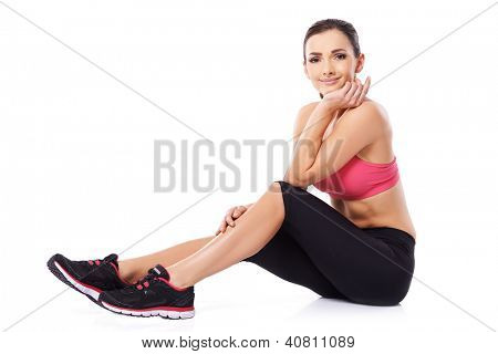 Beautiful young female athlete taking a rest sitting on the floor with her chin on her hand smiling at the camera, studio portrait over white