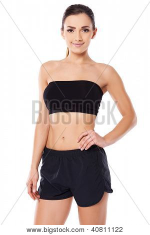 Beautiful woman with a bare midriff in black shorts and a sports bra smiling at the camera, three quarter studio portrait on white