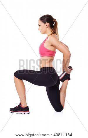 Woman athlete doing a workout kneeling to flex and stretcg her leg muscles for improved mobility, studio portrait on white
