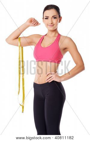 Beautiful slim woman with a lovely smile posing with a tape measure dangling over her raised arm over white