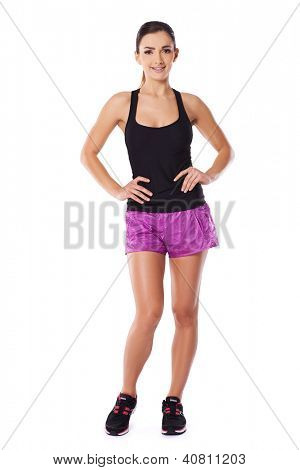 Sexy beautiful woman with a healthy fit body posing in trainers and shorts with her hands on her hips, full length studio portrait over white