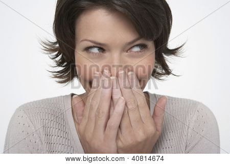 Shy woman covering mouth with hands isolated on white background