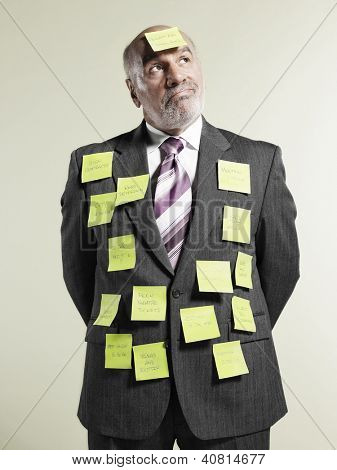 Senior businessman covered with adhesive notes over colored background