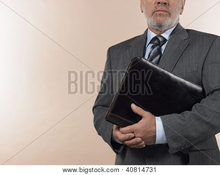 Midsection of senior businessman holding leather binder over colored background