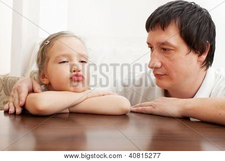 Father comforts a sad girl. Problems in the family