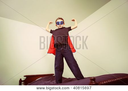 Boy superhero showing his muscles