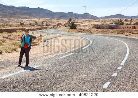 Young Woman On Road With Thumb Lift Up For Hitching Car