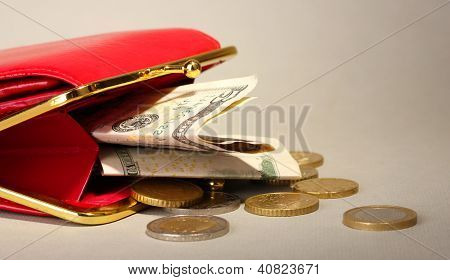 female red wallet with money on grey background