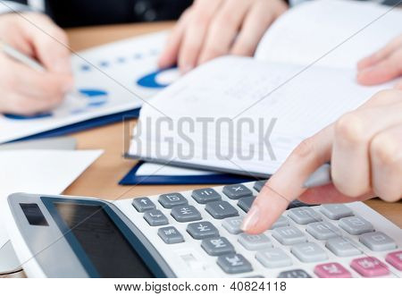 Two business people working sitting at the table. Close up view of hands