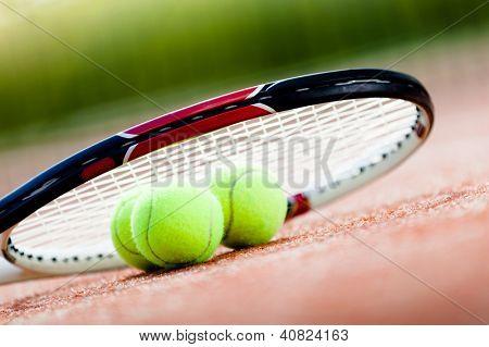 Raqueta de tenis con pelotas en la cancha de tenis