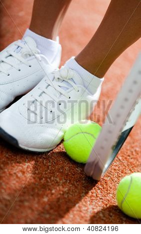 Legs of sporty girl near the tennis racket and balls