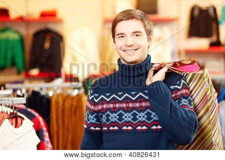 Retrato de homem feliz com paperbags olhando para câmera durante as compras