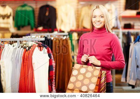 Retrato de menina feliz com paperbags olhando para câmera durante as compras