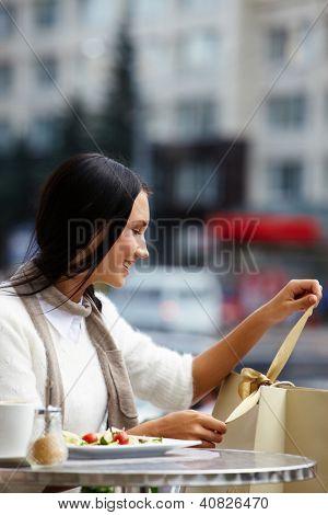Imagem de uma mulher feliz em fita de desembrulhar de café ao ar livre de paperbag em ambiente urbano