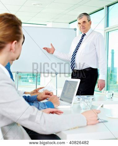 Senior business man showing something on a whiteboard to his colleagues