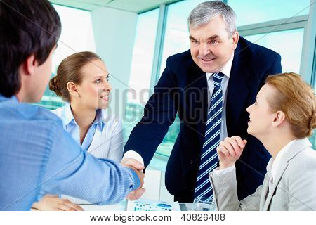 Photo of successful businessmen handshaking after striking deal with partners near by