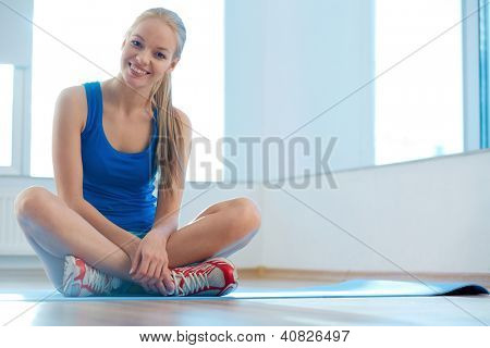 Portrait of happy young woman sitting in gym and looking at camera