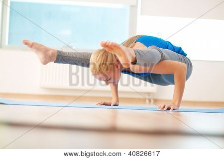 Portrait of young woman doing yoga exercise in gym