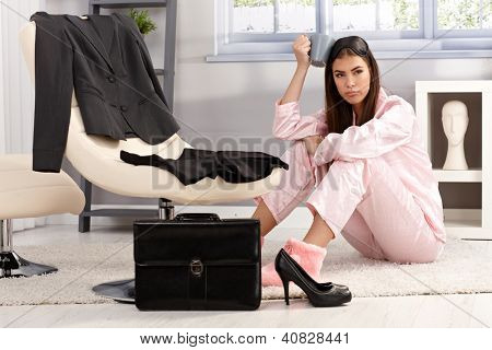 Displeased tired young woman in pyjama getting ready for work, sitting on living room floor surrounded with business clothes and briefcase, having coffee.