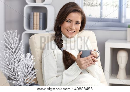 Pretty smiling woman getting warm at winter with tea mug handheld, smiling looking away.
