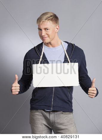 Good news: Smiling man giving thumbs up at white blank signboard with space for text isolated on grey background.